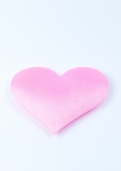 Rosa herz auf weißem hintergrund. valentinstag konzept. liebe und romantisches foto. postkarte für den urlaub. schöne warme tapete mit liebe. weicher fokus. platz kopieren.