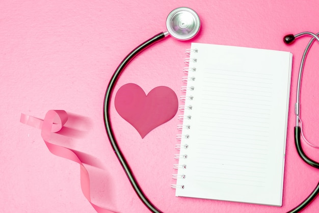 Rosa herz- und bewusstseinsband mit einem stethoskop und einem leeren buch