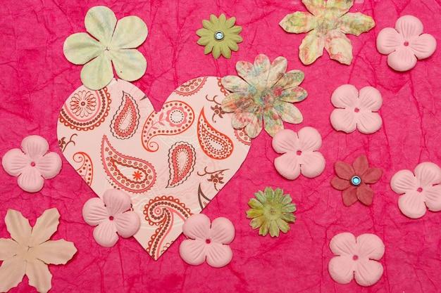 Rosa herz und die papierblumen auf rosa hintergrund