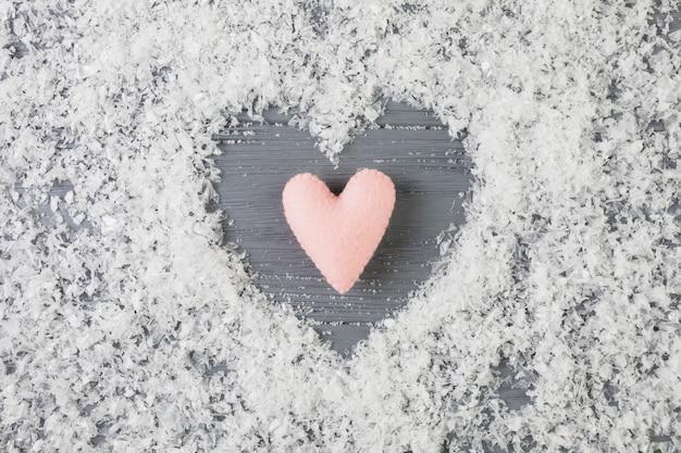 Rosa herz zwischen dekorativem schnee auf hölzernem schreibtisch