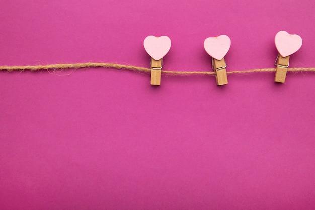 Rosa herzen am seil mit wäscheklammern, auf rosa