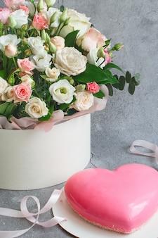 Rosa herzförmiger moussekuchen und ein großer strauß schöner blumen