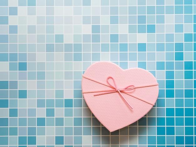 Rosa herzgeschenkbox auf blauem mosaikhintergrund, selektiver fokus, kopienraum. liebe und valentinstag kulisse.