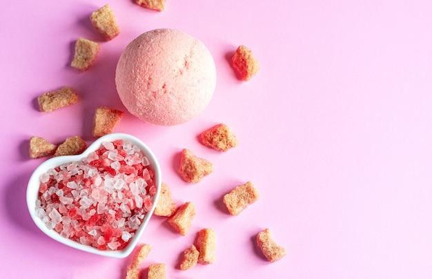 Rosa himalaya-salz auf rosa papierhintergrund in einer herzform-untertasse