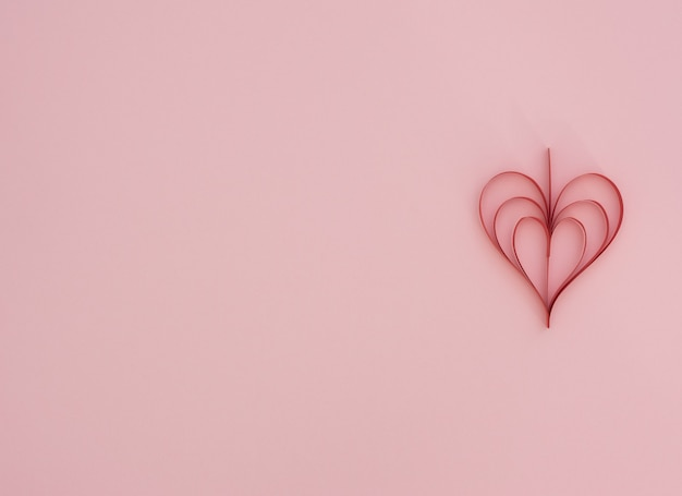 Rosa hintergrund des valentinstags mit handgemachtem rotem papierherz quilling. valentinstag grußkarte. flacher laienstil mit kopierraum. liebes-, glücks- und hochzeitskonzept.
