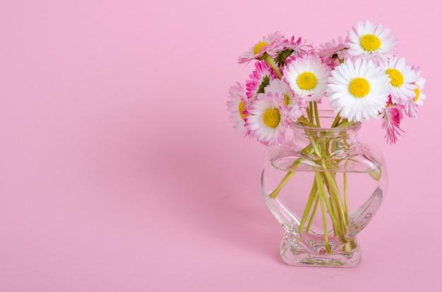 Rosa hintergrund für valentinstagkarte, vase mit blumen in form des herzens.