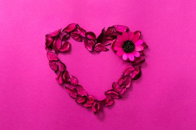 Rosa hintergrund mit herz aus getrockneten blütenblättern und blumen. valentinstag