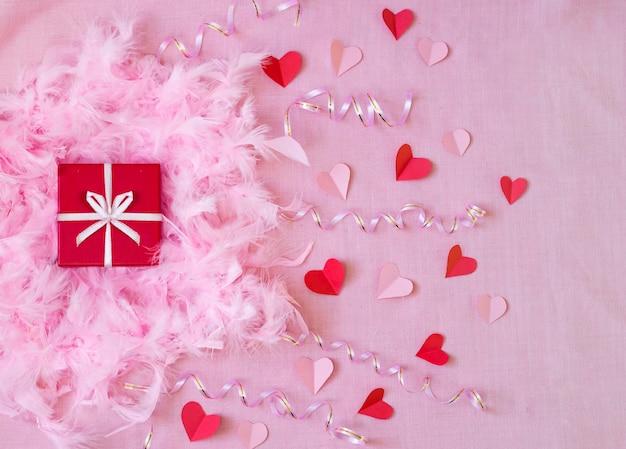 Rosa hintergrund mit rotem geschenk und papierherzen