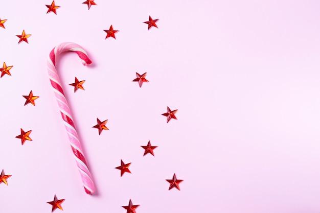Rosa hintergrund mit weihnachtszuckerstange und glänzenden sternen mit kopienraum