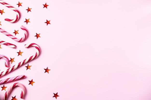 Rosa hintergrund mit weihnachtszuckerstangen, glänzenden roten sternen und kopienraum für ihren text
