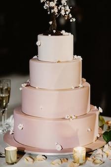 Rosa hochzeitstorte verziert mit kerzen und den rosafarbenen blumenblättern