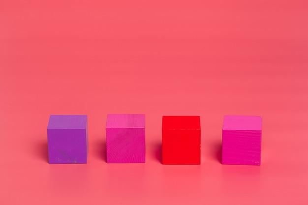 Rosa hölzerne würfel auf rosa farbigem hintergrund