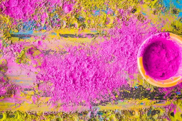 Rosa holi pulver in der schüssel auf hölzernem hintergrund