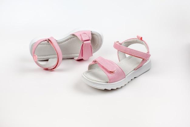 Rosa isolierte sandalen rosa kindersandalen mit weißen sohlen und klettverschlüssen isoliert auf einem...