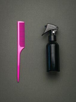 Rosa kämmen und mit haarprodukt auf dunklem hintergrund besprühen. ein werkzeug für die haarpflege. flach liegen.