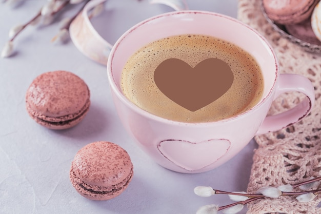 Rosa kaffeetasse mit süßen pastellfarbenen französischen makronen und weidenkätzchen auf hellem tisch von oben