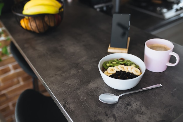 Rosa kaffeetasse, schüssel mit gehackten tropischen früchten kiwi und banane, blaubeeren, löffel und handy auf bartheke in der stilvollen dachbodenküche. unscharfer hintergrund. hochwertiges foto