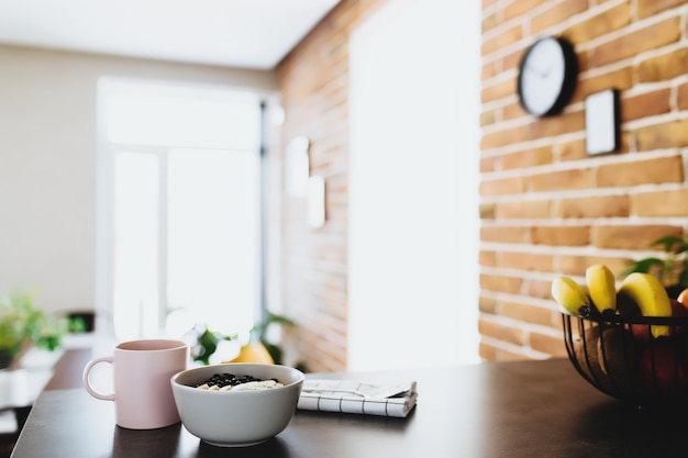 Rosa kaffeetasse, schüssel mit gehackter tropischer frucht kiwi und banane, blaubeeren, löffel auf bartheke in der stilvollen dachbodenküche. unscharfer hintergrund. hochwertiges foto