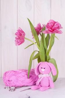 Rosa kaninchen mit tulpen. valentinstag dekor. gestricktes spielzeug, amigurumi, grußkarte.