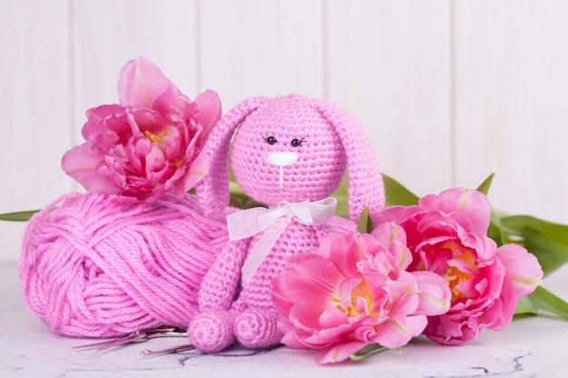 Rosa kaninchen mit tulpen. valentinstag dekor. gestricktes spielzeug, amigurumi, kreativität