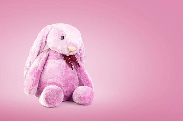 Rosa kaninchenpuppe mit den großen ohren auf süßem hintergrund