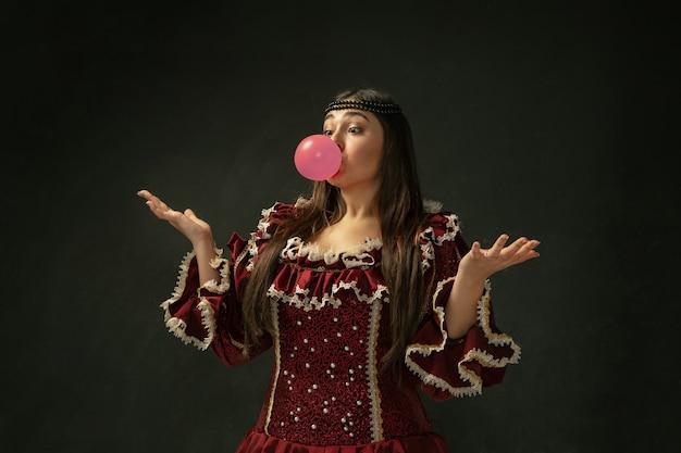 Rosa kaugummi. porträt der mittelalterlichen jungen frau in der roten weinlesekleidung, die auf dunklem hintergrund steht.
