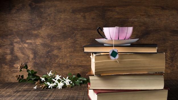 Rosa keramische tasse und untertasse auf dem stapel büchern nahe den weißen blumen und den blättern auf hölzernem schreibtisch