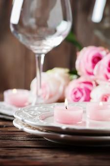 Rosa kerze und rosen auf dem tisch
