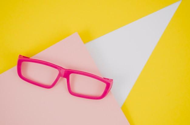 Rosa kinderbrillen auf buntem hintergrund