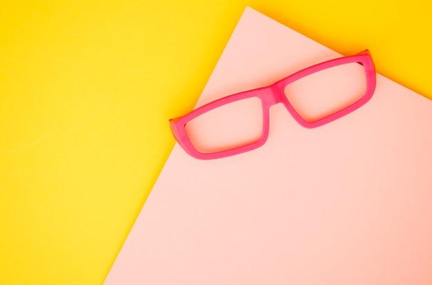Rosa kinderbrillen auf rosa und gelbem hintergrund