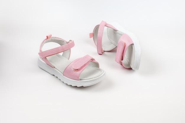 Rosa kindersandalen aus glänzendem leder mit klettverschlüssen flache weiße sohlen isoliert auf einem...