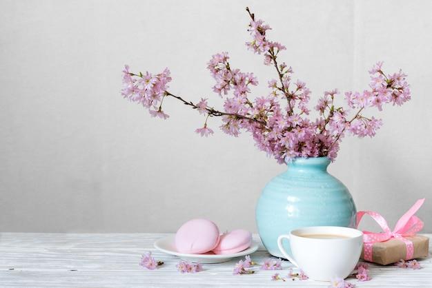 Rosa kirschblütenblumenstrauß mit kaffeetasse, makronen und geschenkbox in blauer weinlesevase