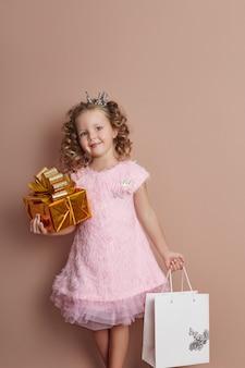 Rosa kleid des kleinen mädchens hält goldgeschenkboxpaket