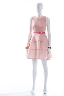 Rosa kleid gürtel auf schaufensterpuppe. weibliche schaufensterpuppe im glänzenden gürtel. lachskleid mit rosa gürtel. stilvolle accessoires und cocktailkleid.