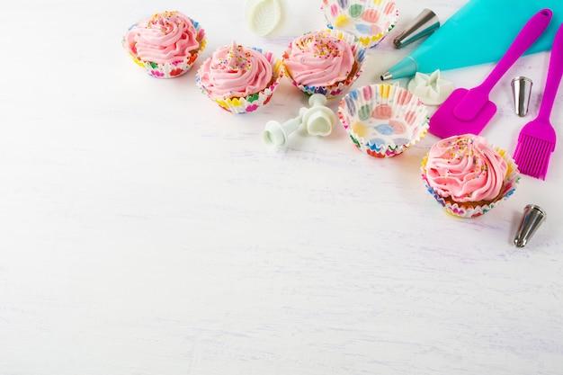 Rosa kleine kuchen und kochgeschirreinladungshintergrund