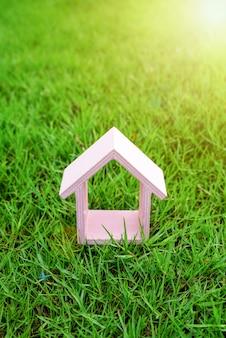 Rosa kleines haus auf dem grünen grasgarten oder park am sonnenlichtmorgen
