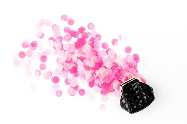 Rosa konfetti fällt aus der handtasche auf weißem hintergrund