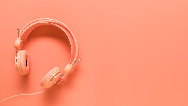 Rosa kopfhörer auf farbiger oberfläche