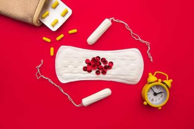 Rosa kosmetikerin mit täglichen baumwollbinden, baumwolltampons und hormonellem verhütungsmittel auf rot.