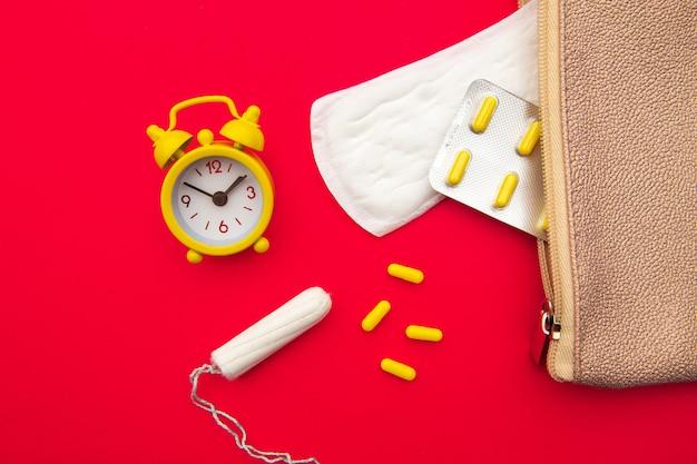 Rosa kosmetikerin mit täglichen baumwollbinden, baumwolltampons und hormonellem verhütungsmittel.