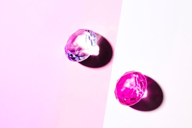 Rosa kristalldiamanten auf rosa und weißem doppelhintergrund