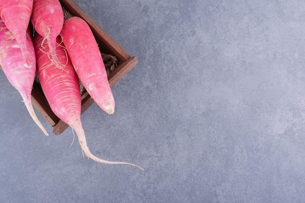 Rosa lange radieschen isoliert auf betonoberfläche