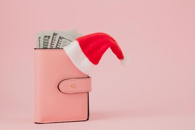 Rosa lederhandtasche mit weihnachtsmannmütze, geschenk, tannenbaum und dollarbanknoten.