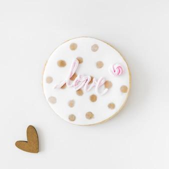 Rosa liebestext auf selbst gemachtem plätzchen mit herzform über weißem hintergrund