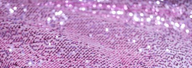 Rosa lila glänzender stoff mit pailletten, abstrakter hintergrund.