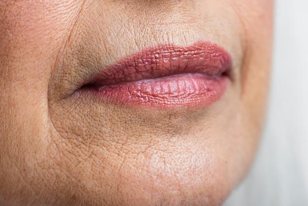 Rosa lippen der reifen frau der nahaufnahme