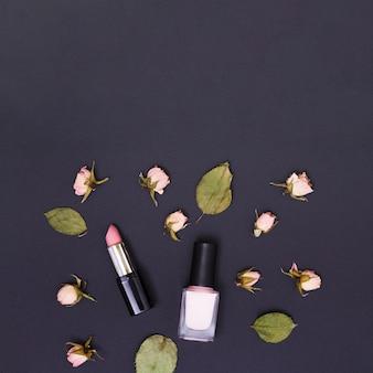 Rosa lippenstift- und nagellackflasche umgeben mit den rosafarbenen rosafarbenen knospen und den blättern auf schwarzem hintergrund