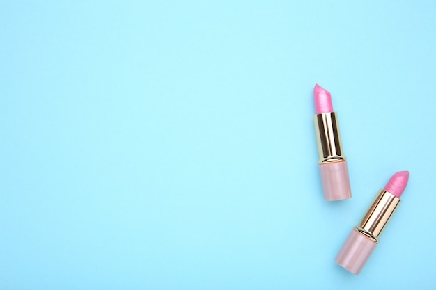 Rosa lippenstifte auf blauem hintergrund, ebenenlage