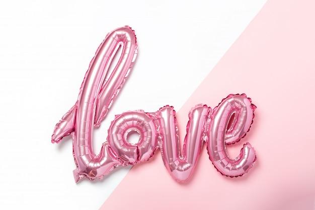 Rosa luftballons in form des wortes liebe auf rosa und weißer farbe