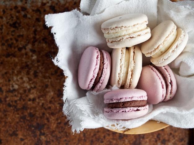 Rosa macaron mit schokoladencremefüllung auf weißem stoff